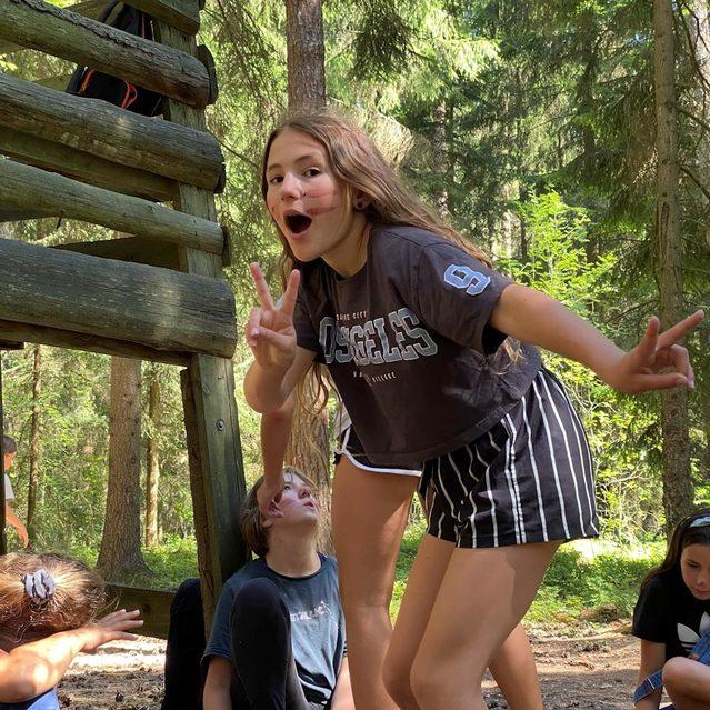Ein Mädchen grüßt im Wald in die Kamera.