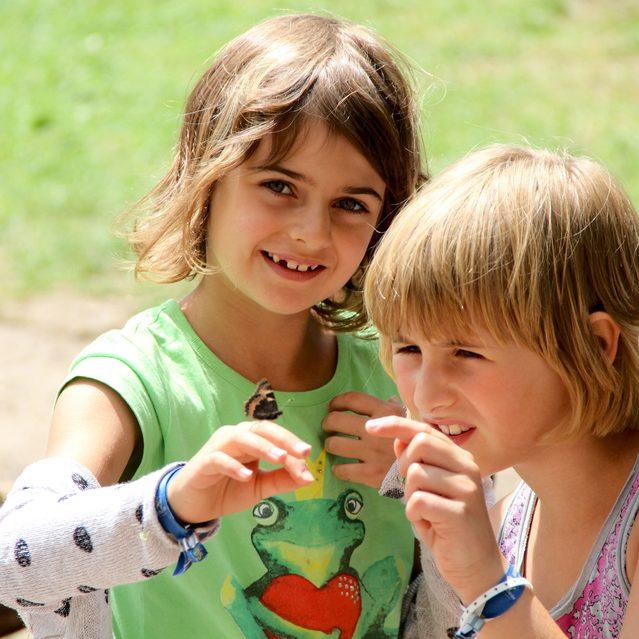 Zwei Mädchen (Kinder) mit einem Schmetterling auf dem Finger