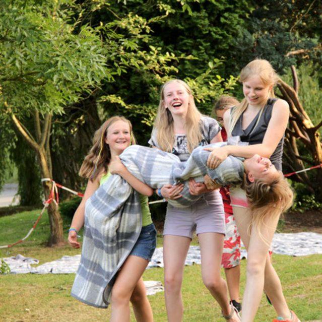 Drei Mädchen tragen ein viertes Mädchen in einer Decke.